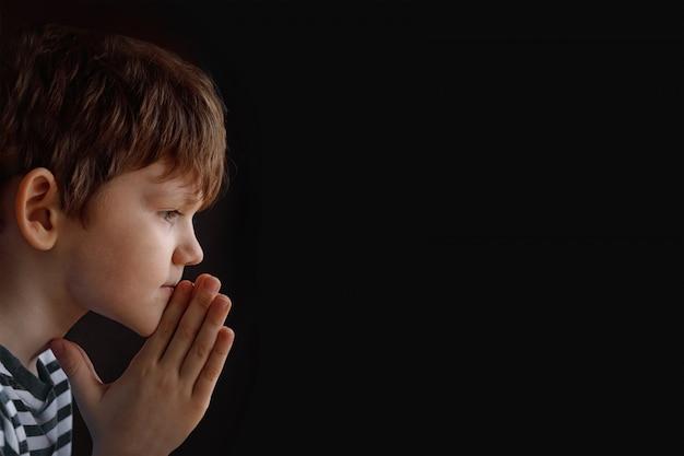 小さな子供は、黒の背景で祈って手を組んだ。