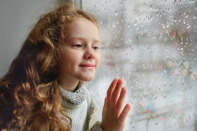 濡れたガラスの秋の悪天候で窓の外見て幸せな子。