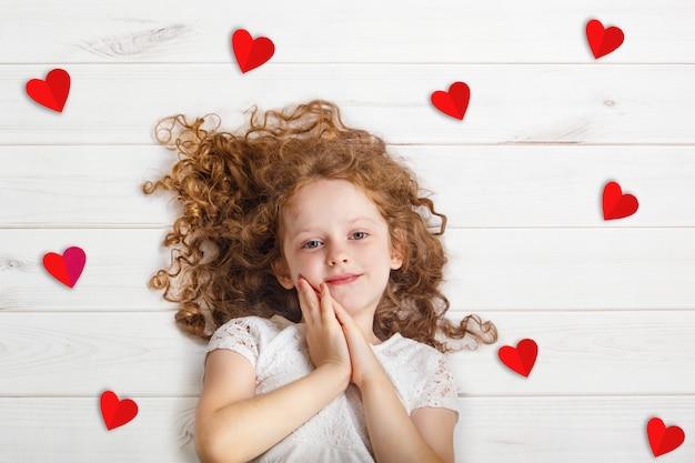 赤い紙の心で木の床に横になっている甘い女の子。バレンタインデーやヘルスケア、医療の概念。
