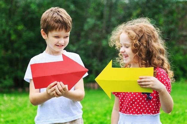 夏の公園で、左右を指している色の矢印を保持している子供たち。子供の頃、友情の概念。