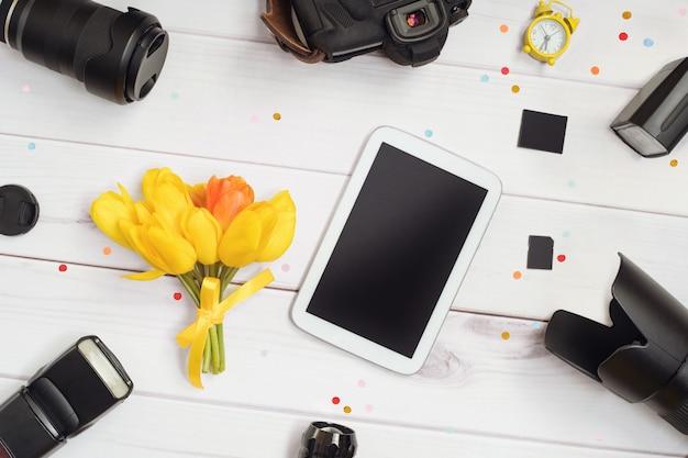 アクセサリー写真家:カメラ、レンズ、フラッシュ、メモリカード、目覚まし時計、タブレット、木製のテーブルの上のチューリップの花束。