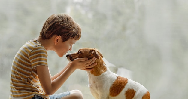 子供が窓の上の鼻に犬をキスします。