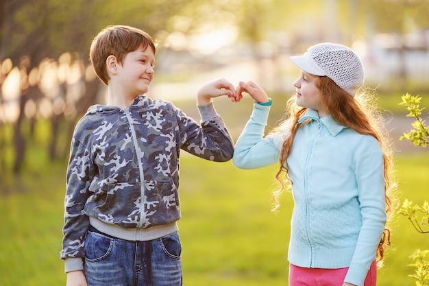 かわいい子供たちは春の屋外でハート形に手を繋いでいます。