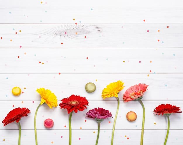 Красные, желтые цветы герберы с конфетти на дереве