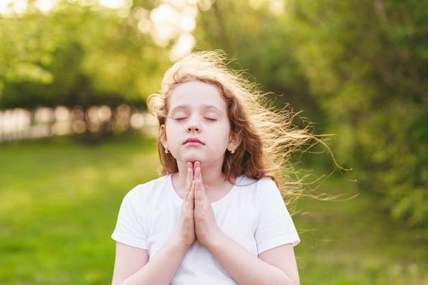 赤毛の女の子は祈りと彼女の手を上げる