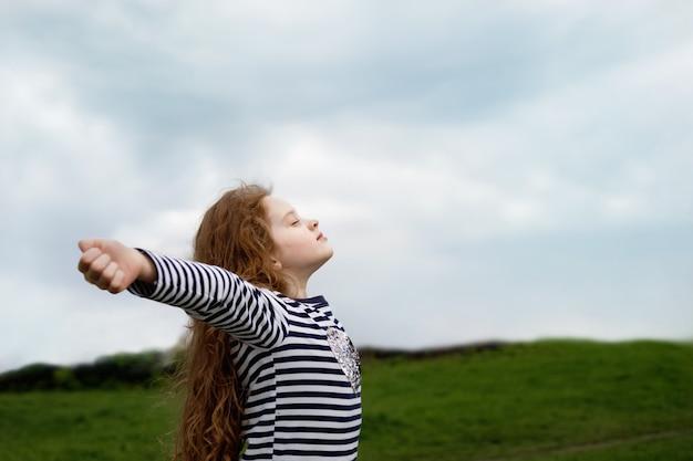 小さな女の子は彼女の目を閉じて新鮮な送風空気で呼吸しています。