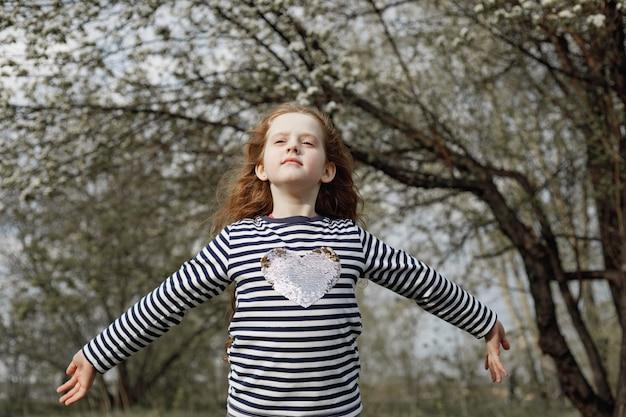 巻き毛の少女が新鮮な空気を吹いて呼吸します。