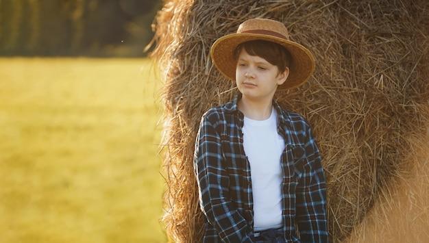 干し草ベール近くに立っている麦わら帽子の少年
