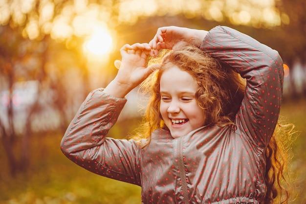 秋の公園で小さな女の子を笑っています。