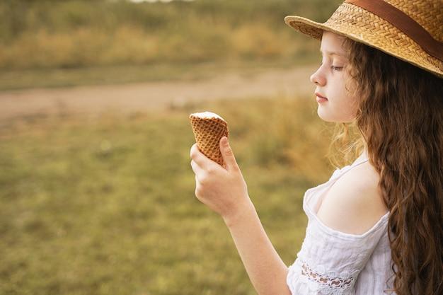 麦わら帽子の巻き毛の少女は、夏に村でアイスクリームを食べる