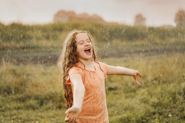 Смеющийся ребенок развел руками и ловит капли дождя.