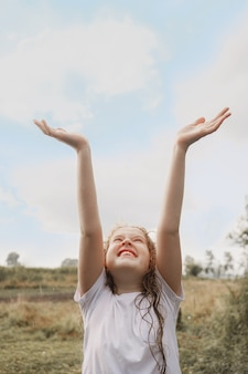 Смеющийся ребенок развел руками и ловит капли дождя и солнечные лучи.