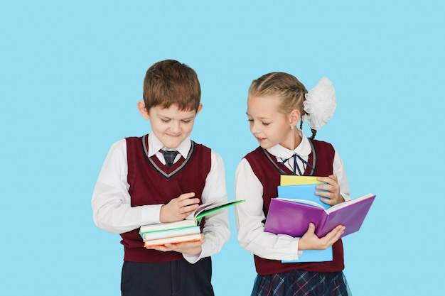 Дети с книгами на голубой стене.