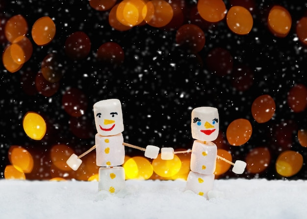 手を繋いでいるマシュマロ雪だるま。休日のコンセプトです。お菓子とクリスマスの背景。