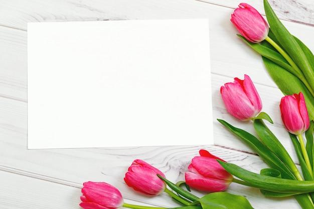 テキストと木製の背景にピンクのチューリップの花束のホワイトペーパー。