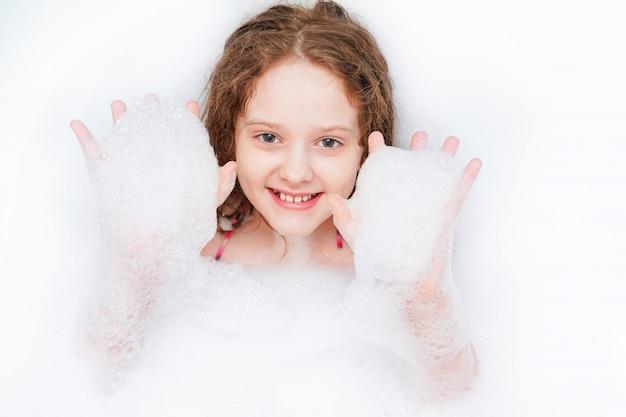 Смеющийся ребенок в окружении пузырьков пены принимает ванну.