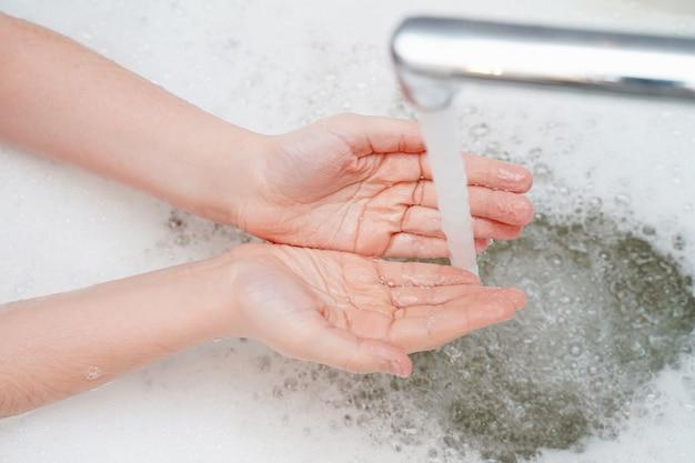 Ребенок моет руку в ванной комнате.