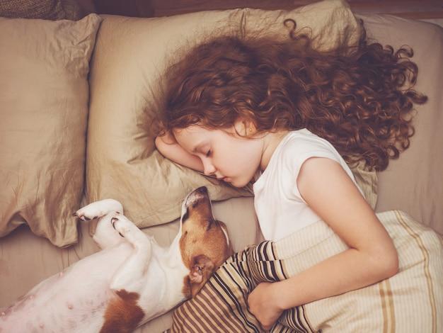 Сладкий ребенок и щенок спит в ночи.