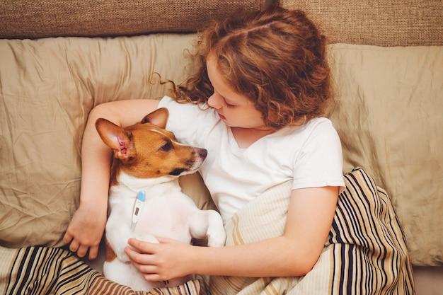 病気の赤ちゃん女の子とキルトの下の子犬
