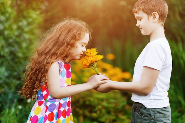 小さな男の子の贈り物は彼の友人の女の子を花します。