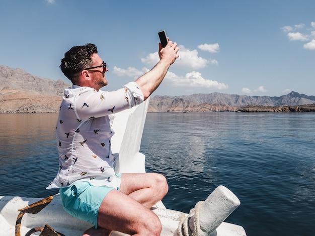ボートに座って魅力的なファッショナブルな男