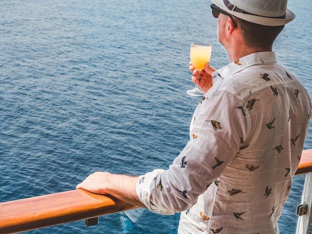 Мужчина держит красивый стакан розового вина