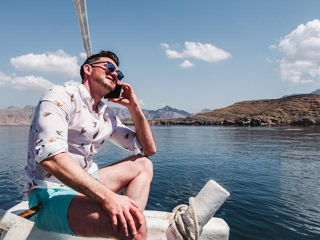 Привлекательный, модный человек сидит на лодке