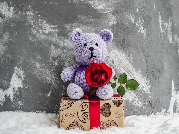 明るいぬいぐるみと咲く赤いバラ