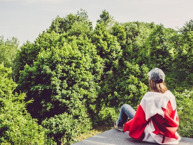 カナダの旗を保持しているかわいい女性。国民の祝日のコンセプト