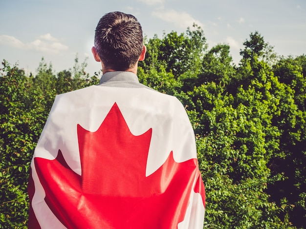 カナダの旗を保持している魅力的な男性。祝日