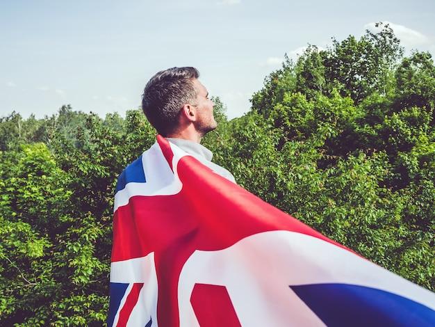 英国の旗を保持している魅力的な男性をクローズアップ