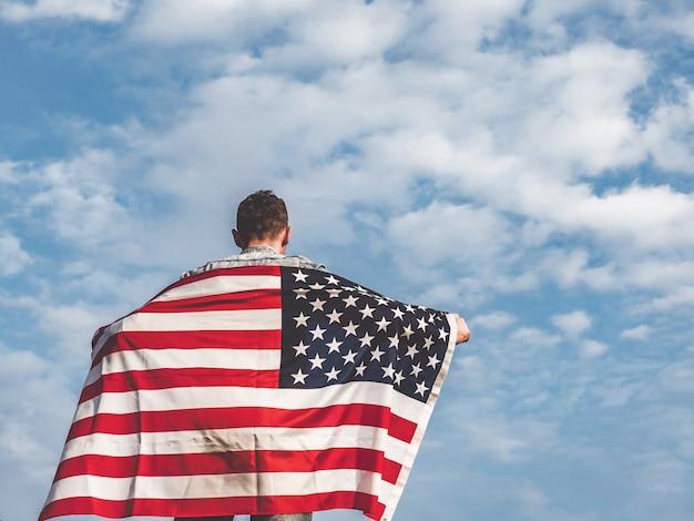 Привлекательный мужчина держит флаг сша