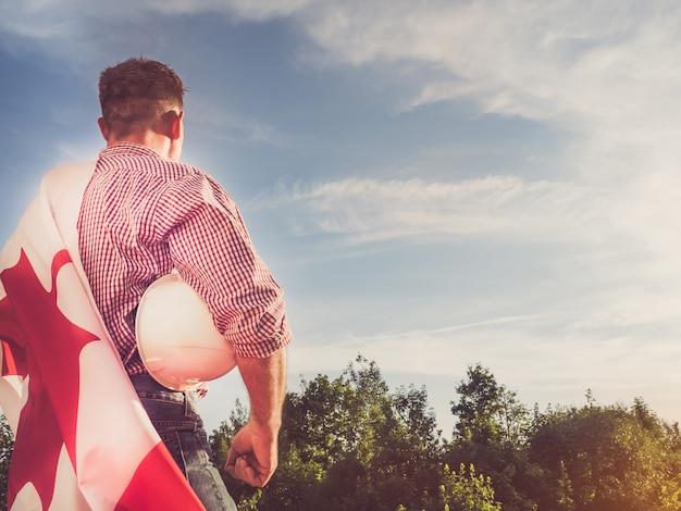 Молодой инженер, белый защитный шлем и канадский флаг