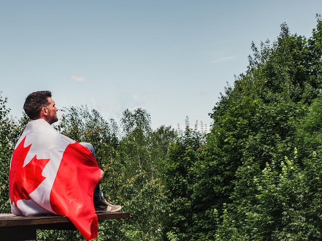 Привлекательный мужчина держит канадский флаг. национальный праздник