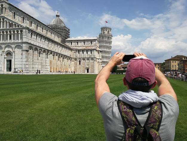 斜塔の写真を撮る携帯電話を持つスタイリッシュな男