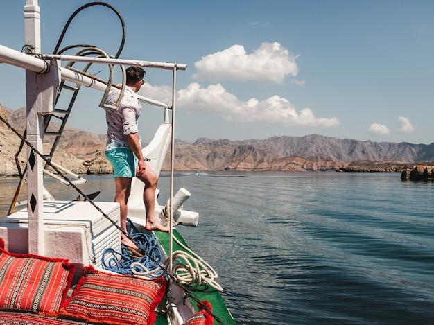 ボートの上に立って魅力的でファッショナブルな男