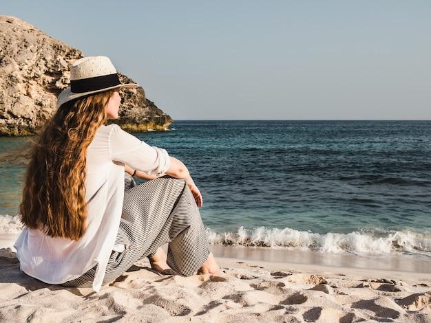 空のビーチに座っているかわいい女