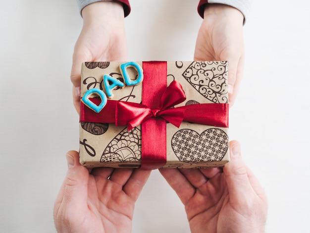 Детские руки и красивая подарочная коробка