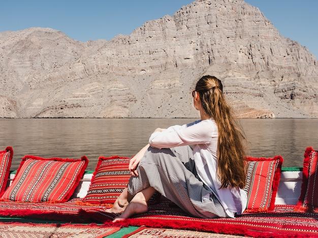 ボートに座っているファッショナブルな女性。オマーンフィヨルド
