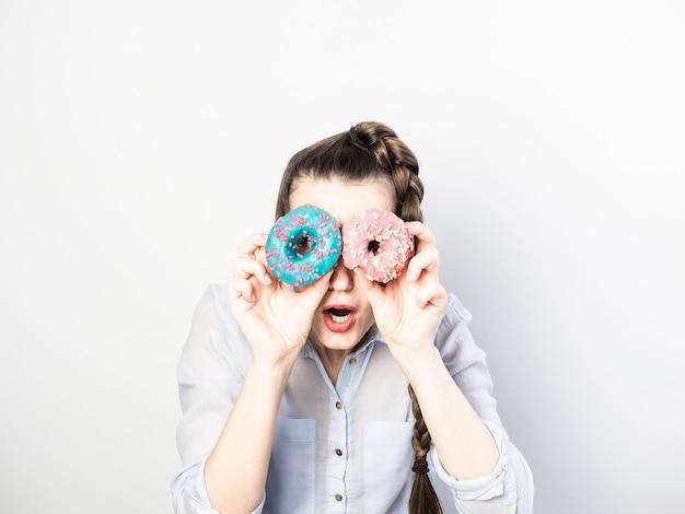 Смешная женщина, держащая красочные пончики