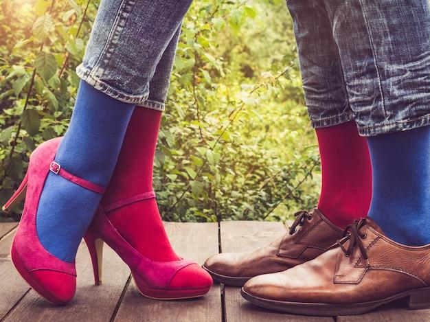 男性と女性の足、明るい靴下。閉じる
