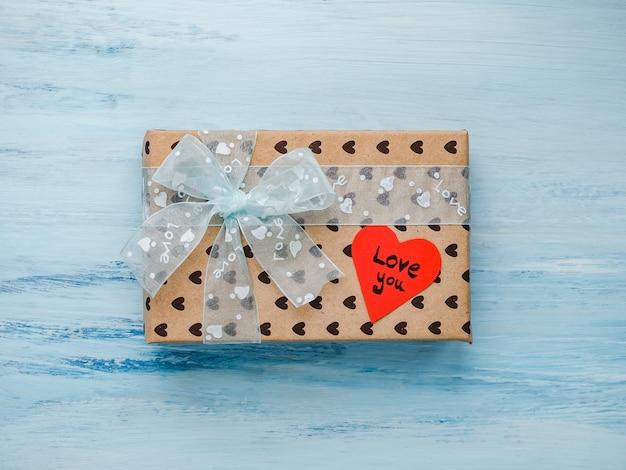 Коробка с подарком, перевязанная лентой, записка со сладкими словами