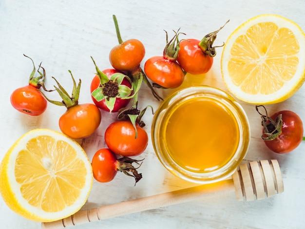 Свежий желтый лимон, кувшин с медом и красными ягодами