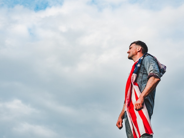 アメリカの国旗を保持しているハンサムな若い男
