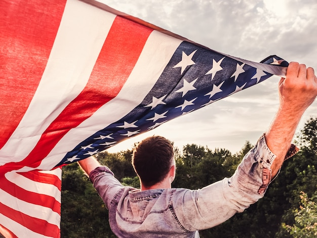 Красивый молодой человек держит американский флаг