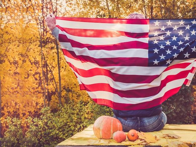 男は米国の旗を握っています。祝日