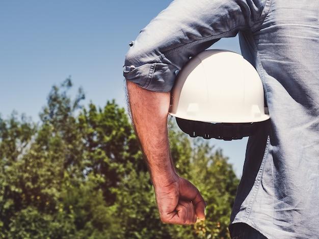 Инженер, держащий белый шлем в парке
