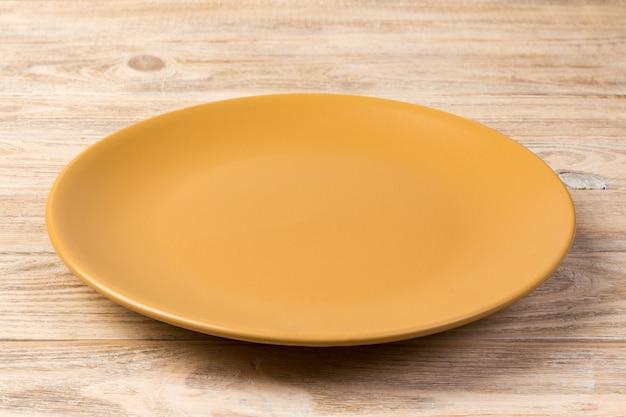 透視図。オレンジ色の木製の背景に夕食のための空のオレンジ色のマットディッシュ