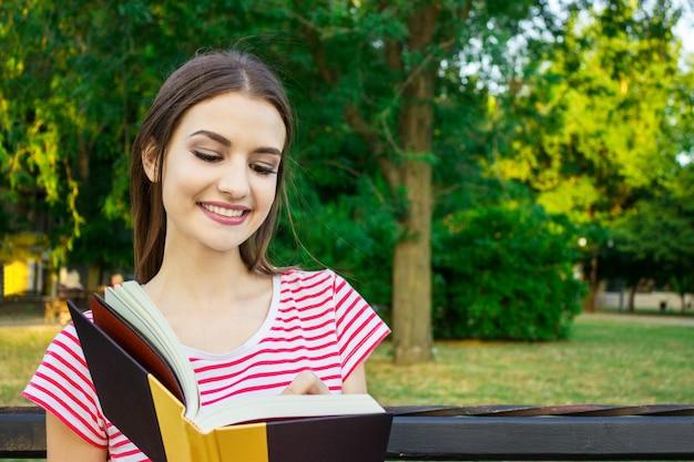 美しい都市公園でいくつかのメモを作る日記と一緒に座っている若い笑顔の女性