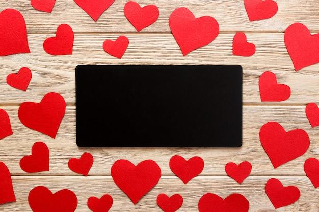 バレンタインデーへのカード。赤いハートと木の上の空の手紙
